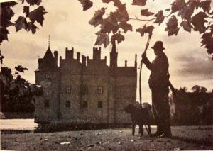 Grev Gregers Ahlefeldt Laurvig Bille med sin langbue, jagthund og Egeskov Slot i baggrunden.